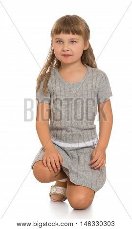 Beautiful little girl blonde in a grey dress . the girl sat down on the floor - Isolated on white background