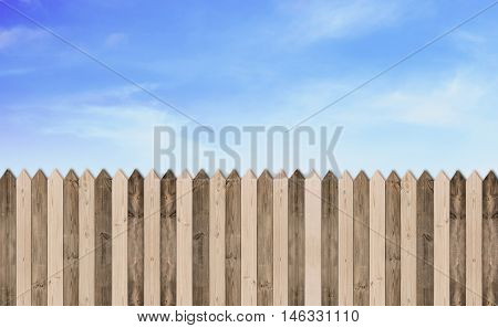 Wooden picket fence with blue sky and clouds