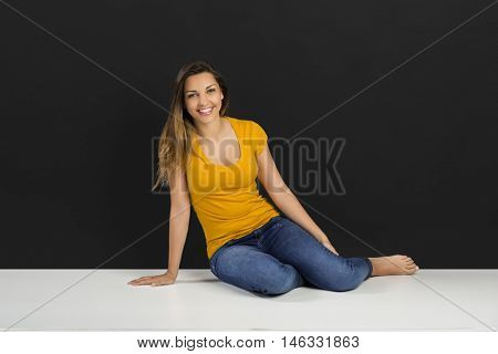 Beautiful young woman sitting in the floor in front of a dark wall