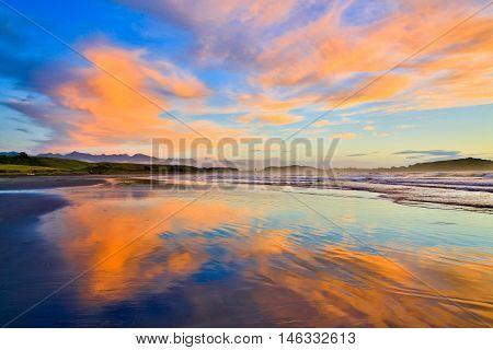 Sandy Beach And Orange Clouds In Westport, New Zealand