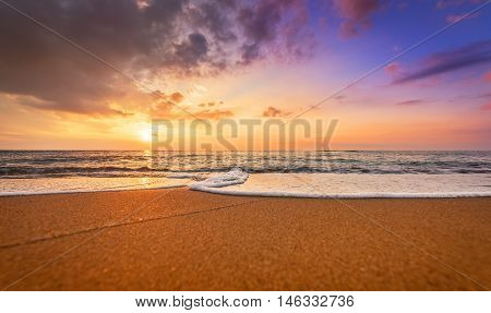 Colorful ocean beach sunrise. Golden sands and dramatic sky
