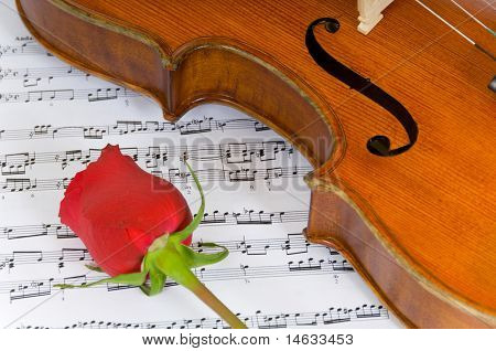 A violin a single red rose and sheet music, image of the beauty of music and the arts