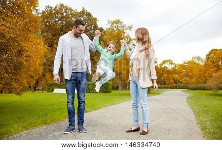 family, parenthood, adoption and people concept - happy mother, father and little girl walking in autumn city park and having fun