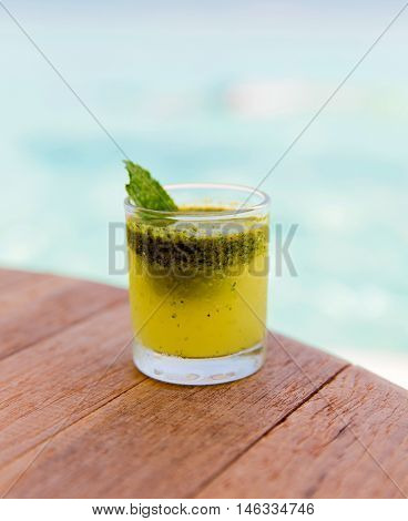 trivet, tourism, drinks and food concept - glass of fresh juice or cocktail on table at beach
