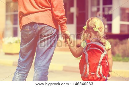 father walking little daughter to school or daycare, learning concept