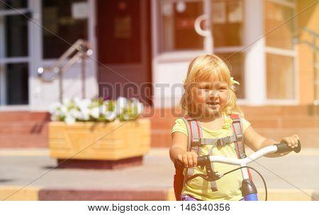 Back to school - little girl biking to preschool or daycare