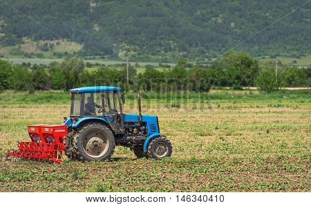 Karlovo Bulgaria - June 01 2016: The 5th open championship of Bulgaria on a plowed land. Young operator plows the site on Belarus tractor in rainy weather.