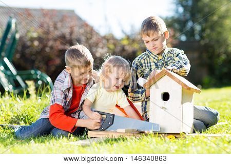 Happy children making wooden birdhouse by hands. Older brother teaches his younger brother.