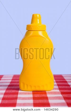 A yellow squeeze bottle in fornt of a blue sky on a  red and white checked or gingham tablecloth with no label