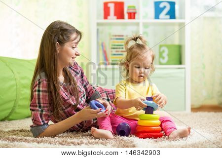Mother and kid girl with toys in playroom
