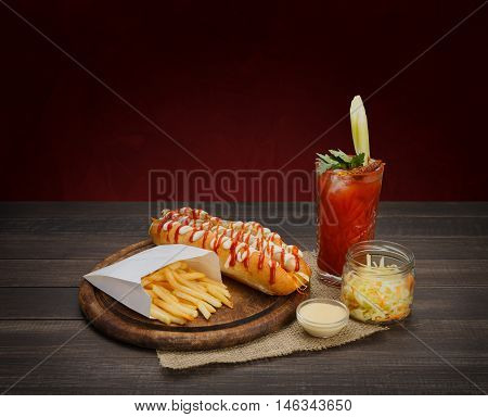 Hot dog and french fries with bloody mary alcohol cocktail and salad. American fast food restaurant cuisine, hotdog, potato chips and drink with celery at wooden desk on table.