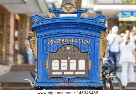Beautiful retro blue mailbox (letterbox) decorated with carved gold-colored figures
