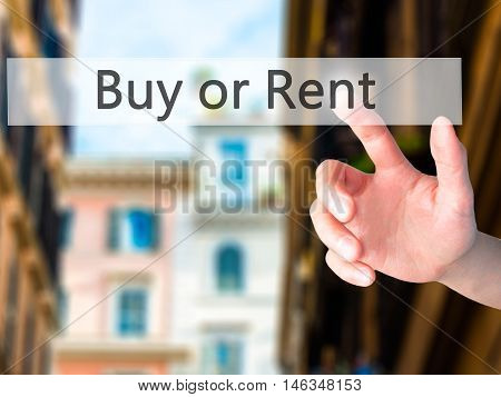 Buy Or Rent - Hand Pressing A Button On Blurred Background Concept On Visual Screen.