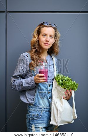 Woman Is Holding In Their Hands Disposable Cup With Smoothies And Bag With Lettuce