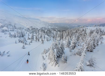 Couple skiing in a groomed curved double ski track with mountain summits and a characteristic cloud formation in the background in the norwegian mountains at easter.