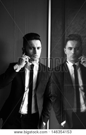 Man young handsome sensual elegant model in suit with skinny necktie open coat talks on mobile phone looks away hand in pocket reflects in mirror black and white on grey background