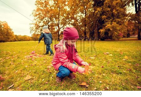 childhood, leisure, friendship and people concept - little girl and boy with rack collecting and racking leaves in autumn park
