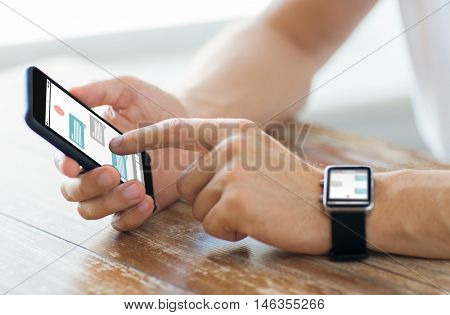 business, technology, online communication and people concept - close up of male hands on wooden table holding smartphone and wearing smart watch with messenger chat on screen