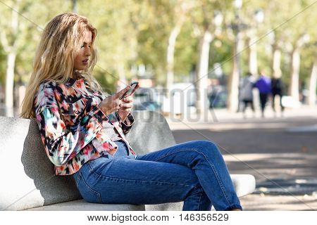 Blonde Woman Sitting On A Bench With Smartphone.
