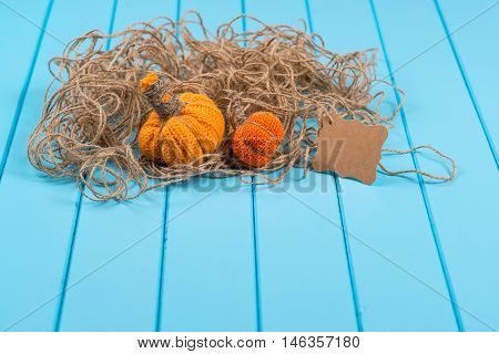 Homemade Halloween pumpkins twine and card on the blue wooden background.