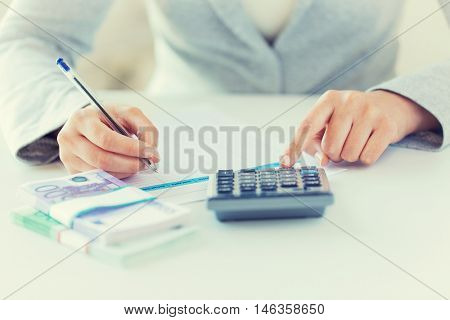 business, finance, tax and people concept - close up of woman hands counting euro money with calculator and tax report form