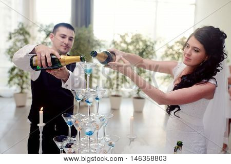 Beautiful wedding couple is pouring champagne indoors. Colorful glasses for alcohol with berries for bride and groom. Beauty of bridal interior for marriage. Bright bar for celebration