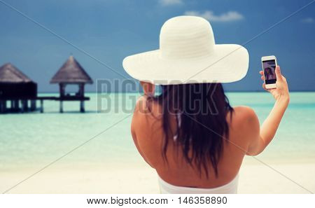 lifestyle, leisure, summer, technology and people concept - smiling young woman or teenage girl in sun hat taking selfie with smartphone over bungalow on beach background