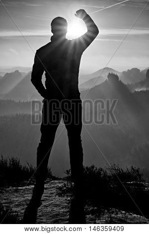 Self Confident Man On Rock Watching Foggy Landscape Up To Horizon