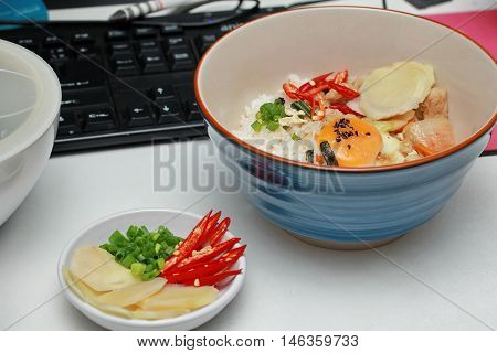Fast food of rice topped boil eggs and fried pork on working desk.