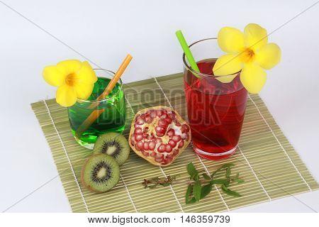 Pomegranate juice and two tone of kiwi juice  with peeled ripe  pomegranate and halves kiwi on bamboo.