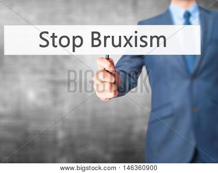 Stop Bruxism - Businessman Hand Holding Sign