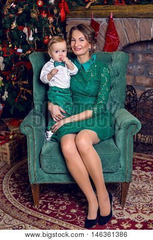 small child sits on the arms of my mother in a white shirt and green pants in the new year