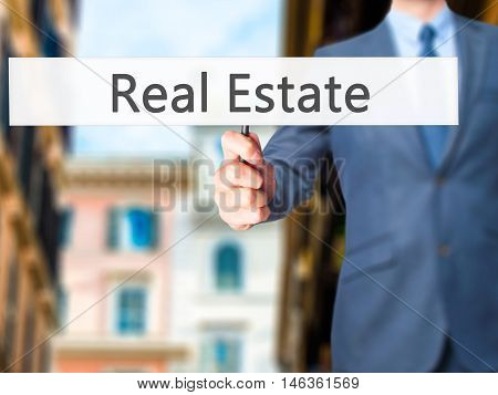 Real Estate - Businessman Hand Holding Sign