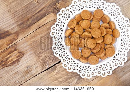 Traditional Dutch candy pepernoot on white plate on wooden background