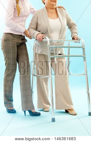 Young woman helping mature woman to make reinstating exercises