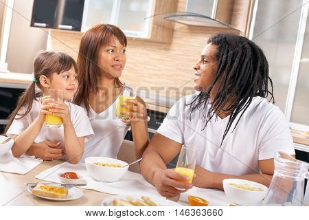 Happy family sitting at the table and having breakfast together