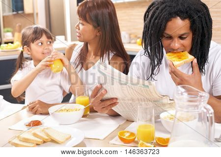 Family of three sitting at the breakfast table and eating