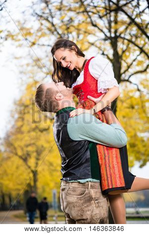 Southern German couple in Tracht in loving embrace, he is lifting her up