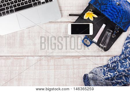 Fashion women accessories. Luxury handmade snakeskin (python) handbag, laptop, smartphone, frangipani. Top view, flat lay, light wooden  background. Free/empty space for text.