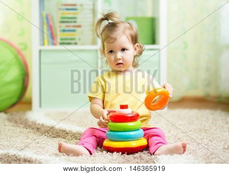 cute baby girl playing with colorful toy at home