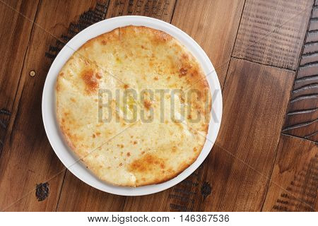 Ossetian pie with potatoes or mutton on a white plate. Wooden background.