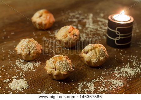 Five salty muffins with sausage, cheese and sesame near candle on wood table.