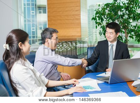 Business meeting Asian people sitting for table with business plan on high floor in the office. Asian nationality male in suit make a deal with businessman partner.