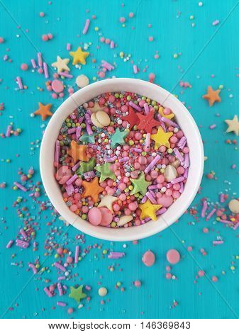 assorted sugar sprinkles in a bowl on a turquoise background