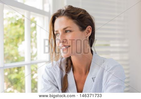 Beautiful mature woman sitting near the window and looking outside. Pensive woman looking out of the window on a bright sunny morning. Woman in nightwear thinking.