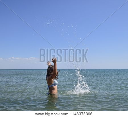 She sprinkles in seawater. Flying up spray from the water throws. The girl with dark hair and a bathing enjoys sea.