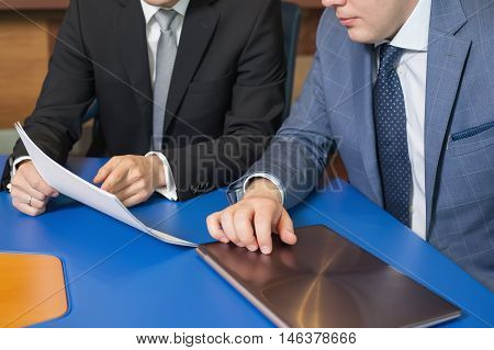 Business meeting People sitting for a glass table with business plan on high floor in the office. Man in suit shows a business graph of his business partner.