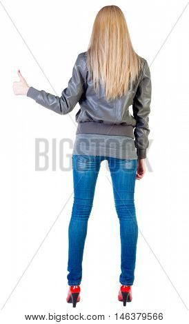back view of standing young blonde woman showing thumb up. beautiful girl in jeans and red kitten heels gesturing ok sign. Rear view people collection.  backside view of person.  Isolated over white