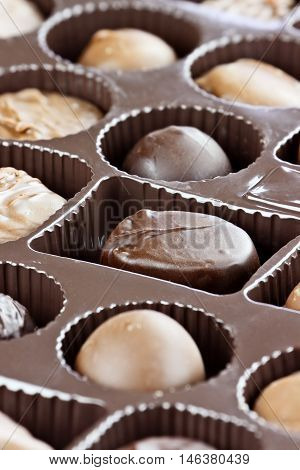 Abstract of a variety of milk and dark chocolate candies. Extreme shallow depth of field with selective focus on center candy.