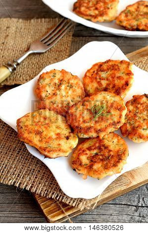 Fried fish cutlets with dill on a plate, fork on old wooden background. Cutlets cooked from minced salmon. Delicious salmon recipe